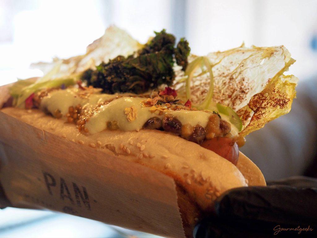 """Hotdog """"Fit for Pan"""" mit Kartoffel- und Hülsenfruchtsalat, Gurkenschaum, Senfkaviar und Kohlchips"""