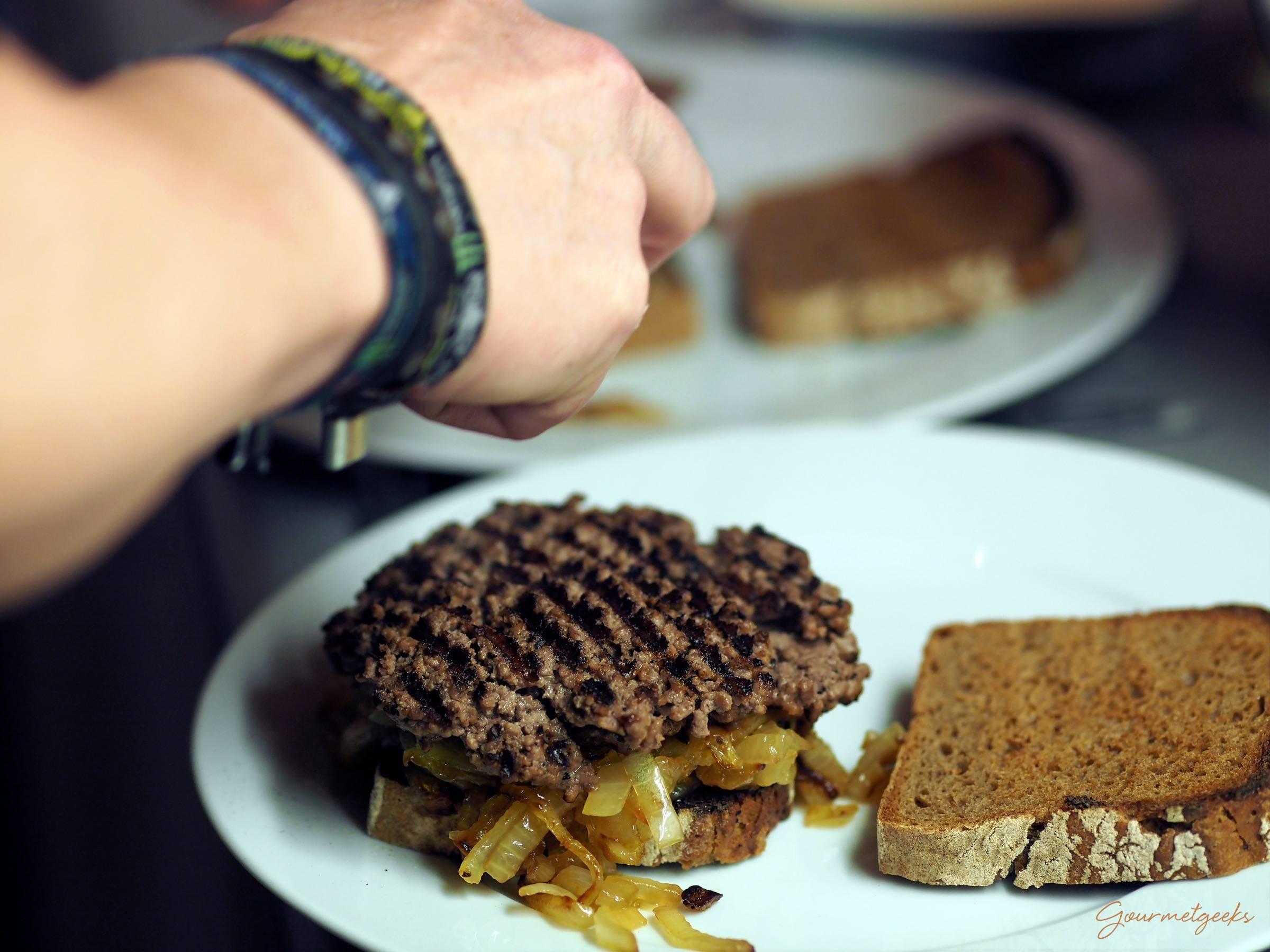 Zwiebeln und Pattie auf's Brot